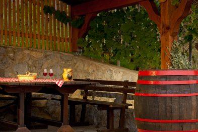 Kozarca in vino v steklenici pred zidanico Meglic